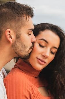 Chłopak całuje kobietę