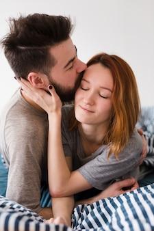 Chłopak całuje swoją dziewczynę na czole z bliska