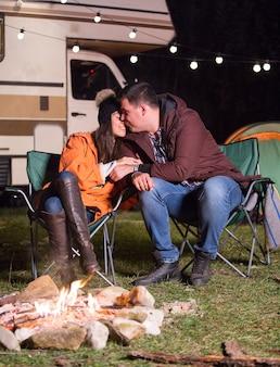 Chłopak całuje swoją dziewczynę w pobliżu ciepłego ogniska w zimną jesienną noc w górach z retro kamperem w tle.