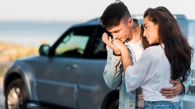 Chłopak całuje swoją dziewczynę w rękę zamazany samochód