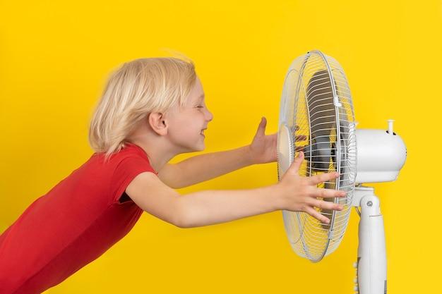 Chłopak chłodzi się wentylatorem. dziecko trzyma wentylator na żółtej przestrzeni. gorąca pogoda.