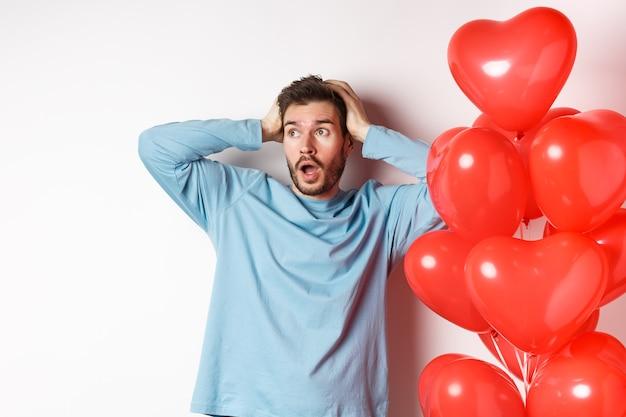 Chłopak chwyta głowę w dłonie i panikuje nad prezentami walentynkowymi, patrząc w bok z zaniepokojoną twarzą, stojąc w pobliżu balonów w kształcie serca i myśląc o prezentach dla kochanka, białe tło.