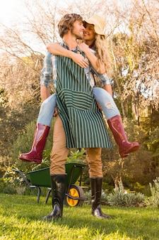 Chłopak daje piggyback dziewczynie w ogrodzie