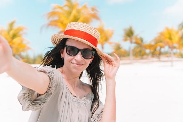 Chłopak dziewczyny po trzymając się za ręce na białej dzikiej plaży, śmiejąc się i uśmiechając