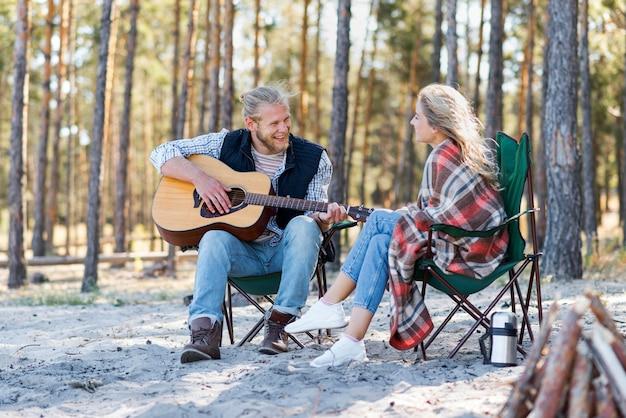 Chłopak gra na gitarze akustycznej dla swojej dziewczyny