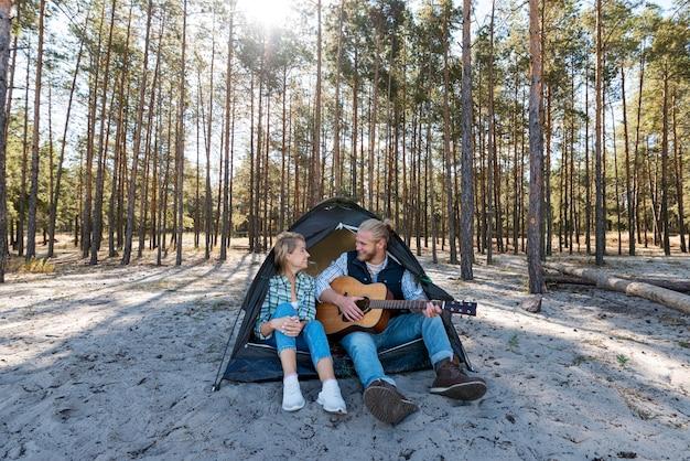 Chłopak gra na gitarze akustycznej długi widok