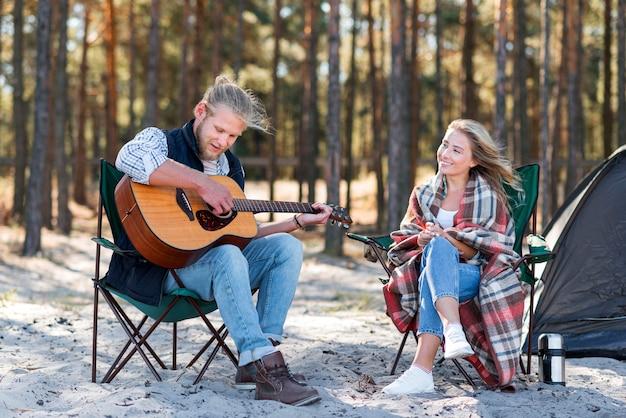 Chłopak gra na gitarze akustycznej i siedzi na krześle