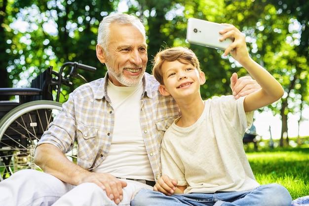 Chłopak i dziadek robią selfie. piknik rodzinny.