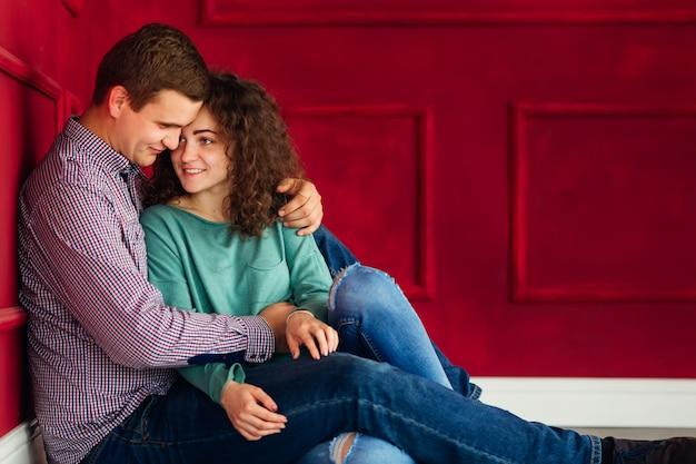 Chłopak i jego dziewczyna siedzą na podłodze w czerwonym pokoju
