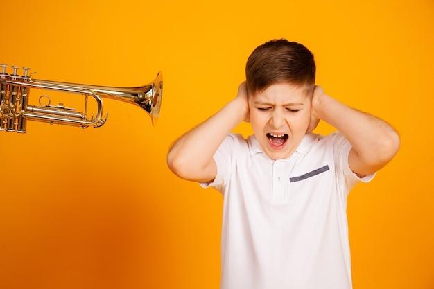 Chłopak jest niezadowolony z irytacji głośnego dźwięku, zamknął uszy dłońmi i krzyczy