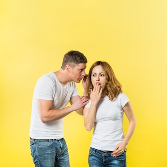 Chłopak mówi zaskakującego sekret jego dziewczyna ucho przeciw żółtemu tłu