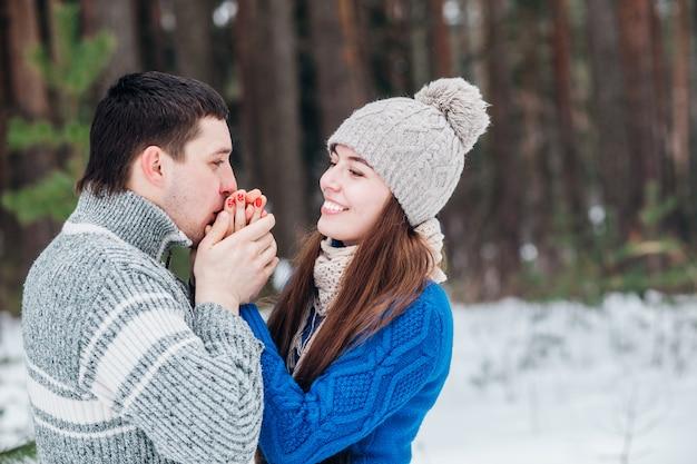 Chłopak ogrzewa dłonie kochanie, zamrożone na zimno