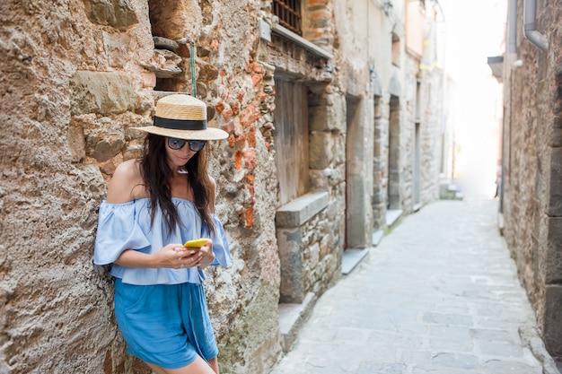 Chłopak podążając za dziewczyną trzymając handsin starej ulicy europejskiej, śmiejąc się i uśmiechając