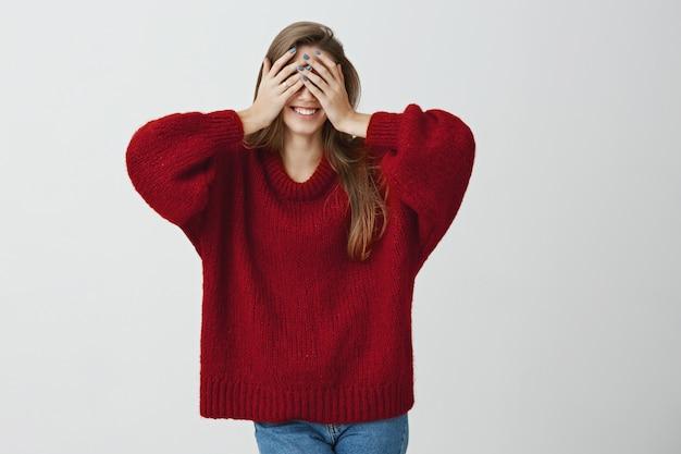 Chłopak przygotował świetny prezent dla swojej miłości. studio ujęć emocjonalną uroczą kobietą w modnych ubraniach zakrywających oczy dłońmi, uśmiechając się szeroko, czekających na coś dobrego