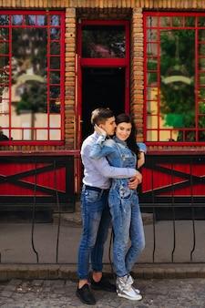 Chłopak przytula kobietę, która opiera się o płot. zakochana para na ulicy