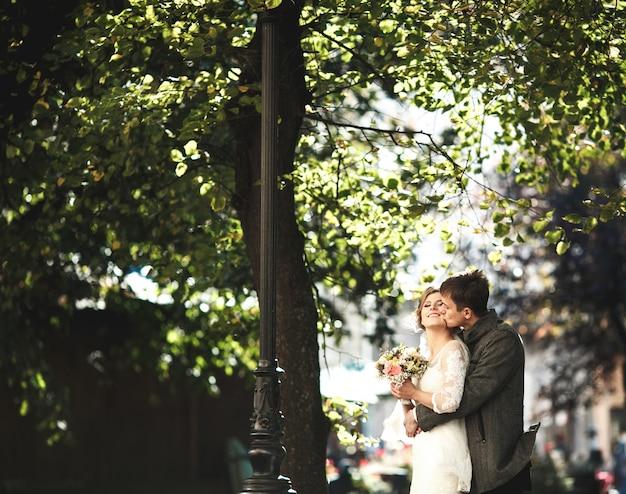 Chłopak przytulając swoją dziewczynę od tyłu i całując ją