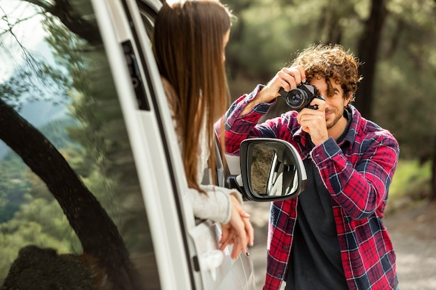 Chłopak robi zdjęcia dziewczynie w samochodzie podczas podróży