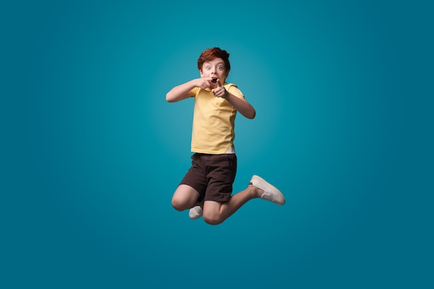 Chłopak skacze na niebieskiej ścianie studia, wskazując i wskazując do przodu