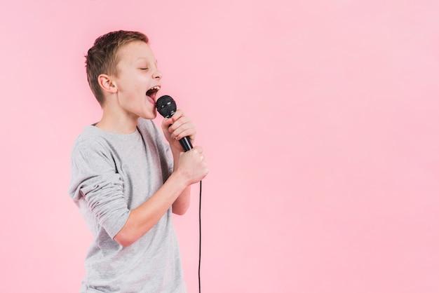Chłopak śpiewa piosenkę na mikrofonie stojąc przed różowym tle