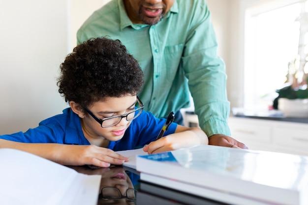 Chłopak uczący się w domu przez ojca w nowej normie