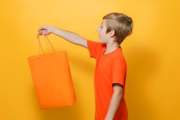 Chłopak wyciągnął rękę do boku, w którym trzyma pomarańczową torbę na zakupy