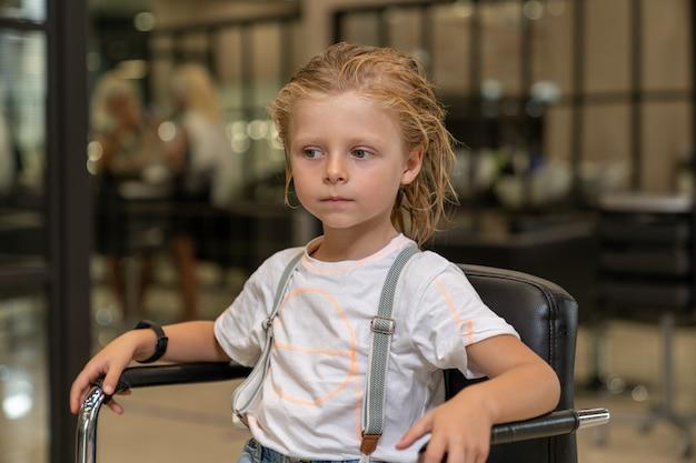 Chłopak z mokrymi włosami siedzi na krześle u fryzjera, czekając na rozpoczęcie strzyżenia