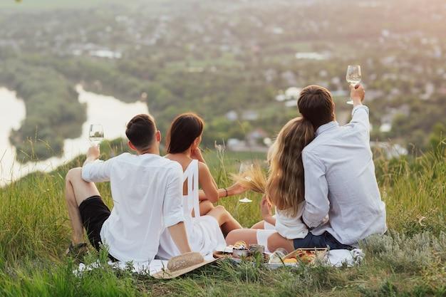 Chłopaki i kobiety na romantycznym pikniku, siedząc przy koszu z owocami i pijąc białe wino z kieliszków.