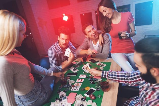 Chłopaki siedzą i grają w pokera, a dziewczyny siedzą na stole