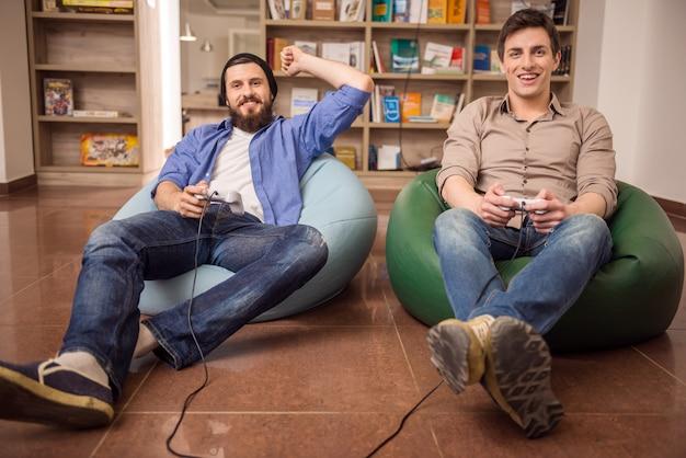 Chłopaki siedzą na pufach i grają razem w gry wideo.