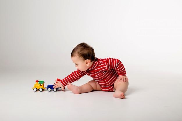 Chłopca w czerwonym body siedzi bawiąc się zabawką na białej ścianie