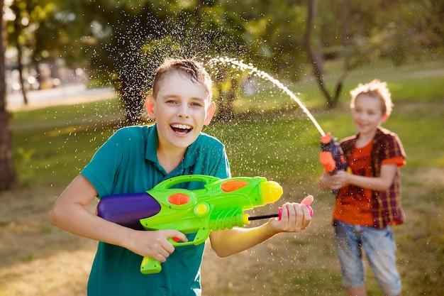 Chłopcy bawią się grając z pistoletami na wodę