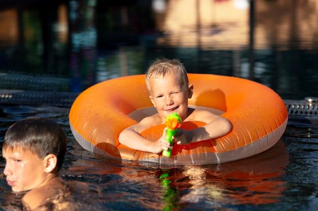 Chłopcy bawią się na basenie z pływakiem i pistoletem na wodę