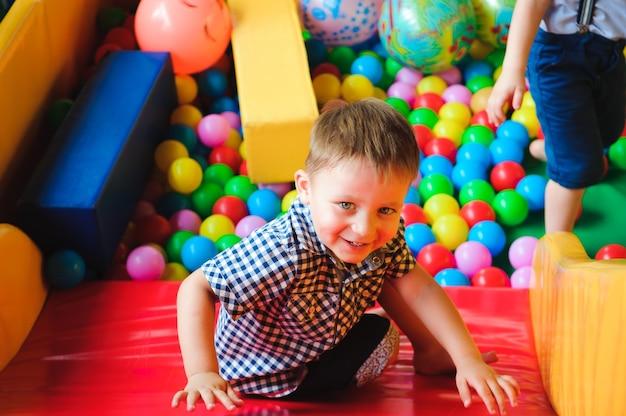 Chłopcy bawią się na placu zabaw, w labiryncie dla dzieci z piłeczkami. kulki wielokolorowe.