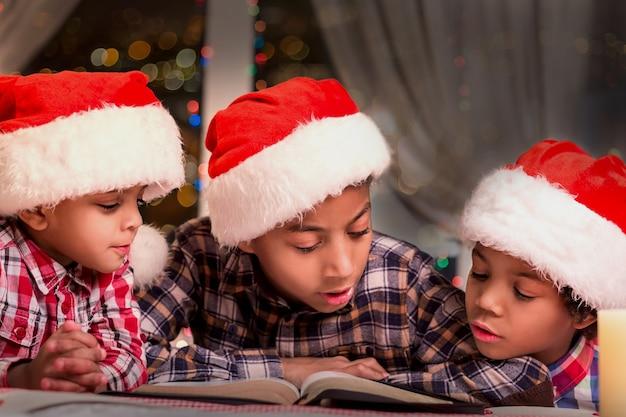 Chłopcy czytanie książki na boże narodzenie. dzieci w santa hats czytanie. czytanie historii bożonarodzeniowych w nocy. spokojna wakacyjna atmosfera.