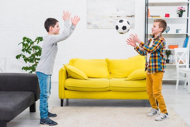 Chłopcy grają w piłkę nożną w salonie