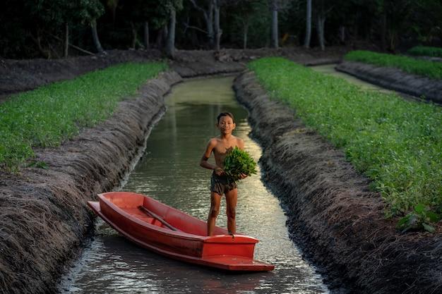 Chłopcy grający na farmie warzywnej w pobliżu pływającego targu damnoen saduak w prowincji ratchaburi