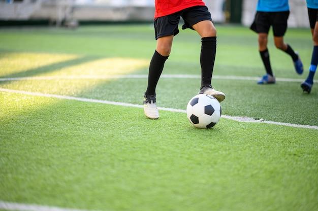 Chłopcy grający w piłkę nożną na boisku treningowym