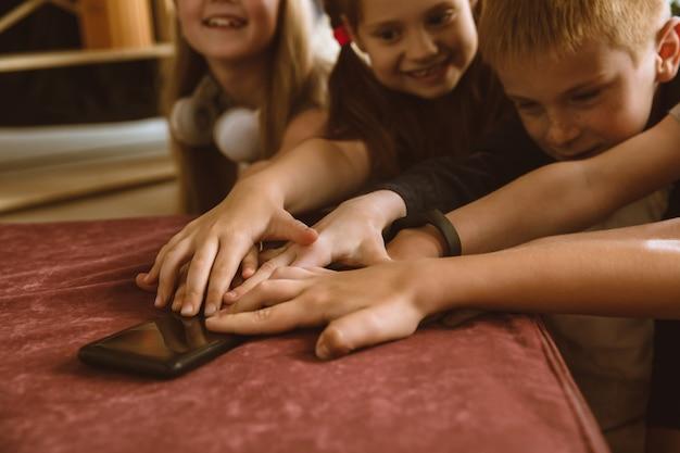 Chłopcy i dziewczęta korzystający z różnych gadżetów w domu. childs z inteligentnymi zegarkami, smartfonem i słuchawkami. robienie selfie, czatowanie, granie, oglądanie filmów. interakcja dzieciaków z nowoczesnymi technologiami.