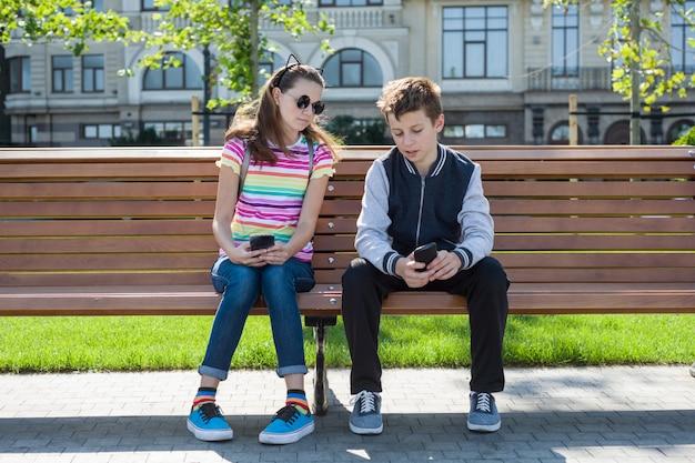 Chłopcy i dziewczęta nastolatki grają, spójrz na smartfona