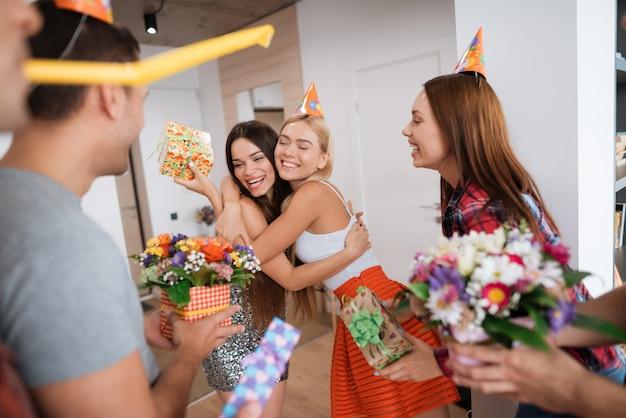 Chłopcy i dziewczęta spotykają urodzinową dziewczynę z prezentami.