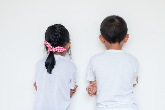 Chłopcy i dziewczęta stoją przed ścianą w rogu pokoju