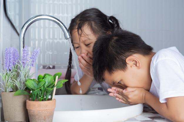Chłopcy i dziewczęta szczotkują zęby.