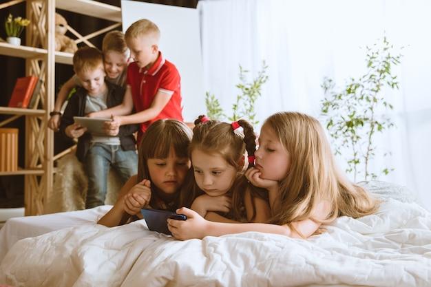 Chłopcy i dziewczęta używający różnych gadżetów w domu