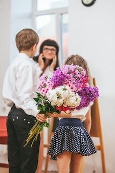 Chłopcy i dziewczynki dają kwiaty jako nauczyciel w dniu nauczyciela