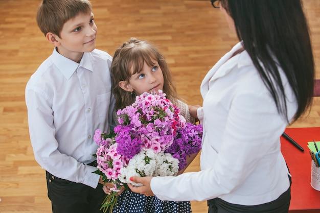 Chłopcy i dziewczynki dają kwiaty jako nauczyciel w szkole