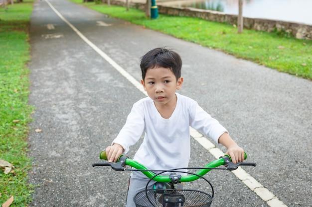 Chłopcy jeżdżą na rowerze po parku zdrowia