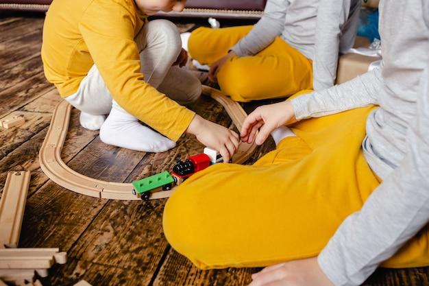 Chłopcy maluchów budują kolej i bawią się drewnianym pociągiem, siedząc na podłodze w salonie.