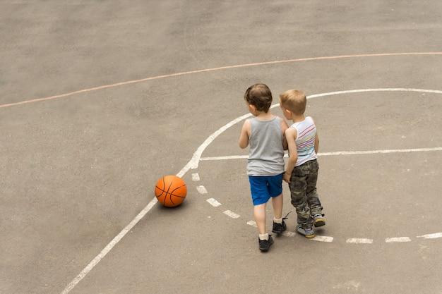 Chłopcy na boisku do koszykówki stoją blisko siebie i patrzą na piłkę leżącą na ziemi