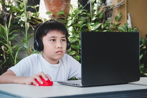 Chłopcy noszą bezprzewodowe słuchawki i używają laptopów do nauki online i przeszukiwania internetu