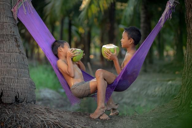 Chłopcy piją świeży sok kokosowy w ogrodzie kokosowym w pobliżu pływającego targu damnoen saduak w prowincji ratchaburi